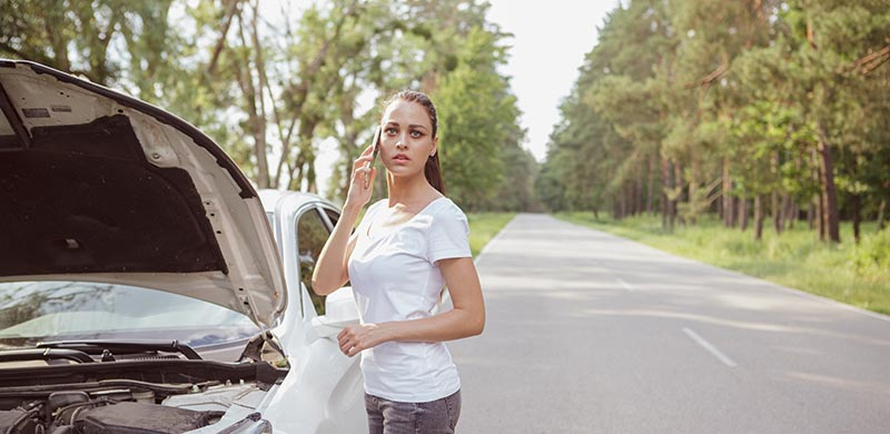 Beautiful young woman calling for help, standing near her broken down car on the side of the road, copy space. Worried young woman using smart phone, calling roadside assistance, standing near her auto with open hood