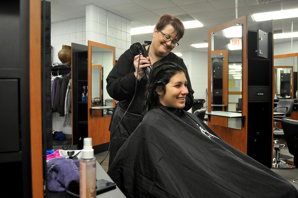 Yvonne Donah blow drys fellow cosmetology student Morgan Myer-Senkarik's hair at the salon.