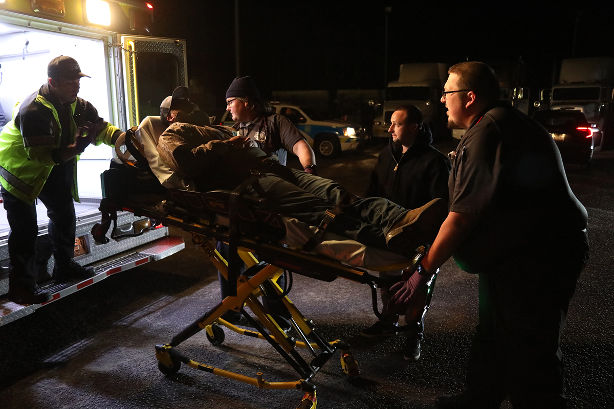 Johnston Community College paramedic interns Tyler McRorie, Torin Laffredo and Christopher Reason load a simulated patient into the ambulance during their Night Ops Exercise.
