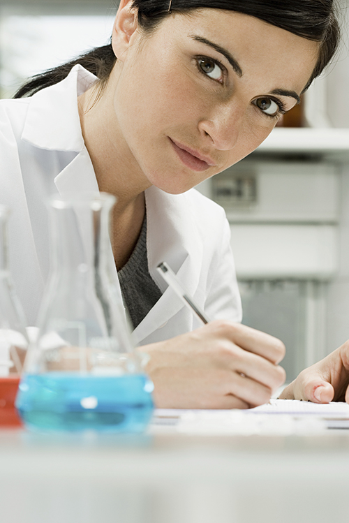 Photo of a scientist completing paper work in a lab